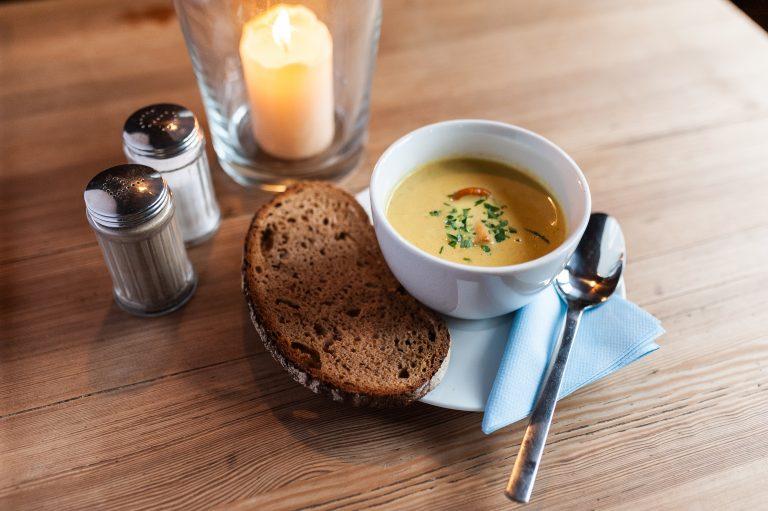 Schälchen Suppe mit Scheibe Brot auf einem Holztisch, nebst Kerze, Salz & Pfeffer