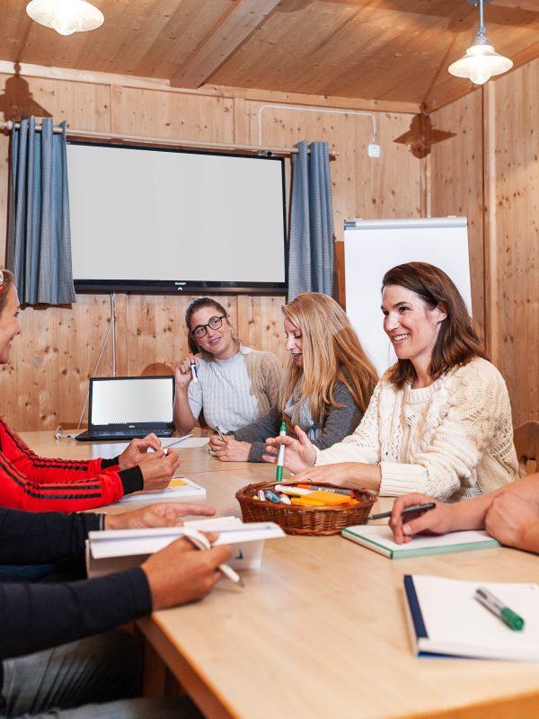 Tagungsgruppe sitzt mit einem gemeinsamen Laptop, Stiften und Papier an einem Tisch, im Hintergrund der TV-Screen und ein Flipchart