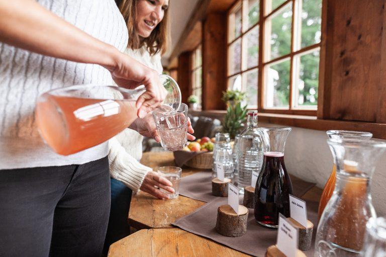 Zwei Kolleginnen gießen sich Saft ins Glas an einem Holztisch, auf dem ein Obstkorb und diverse Getränke aufgebaut sind.