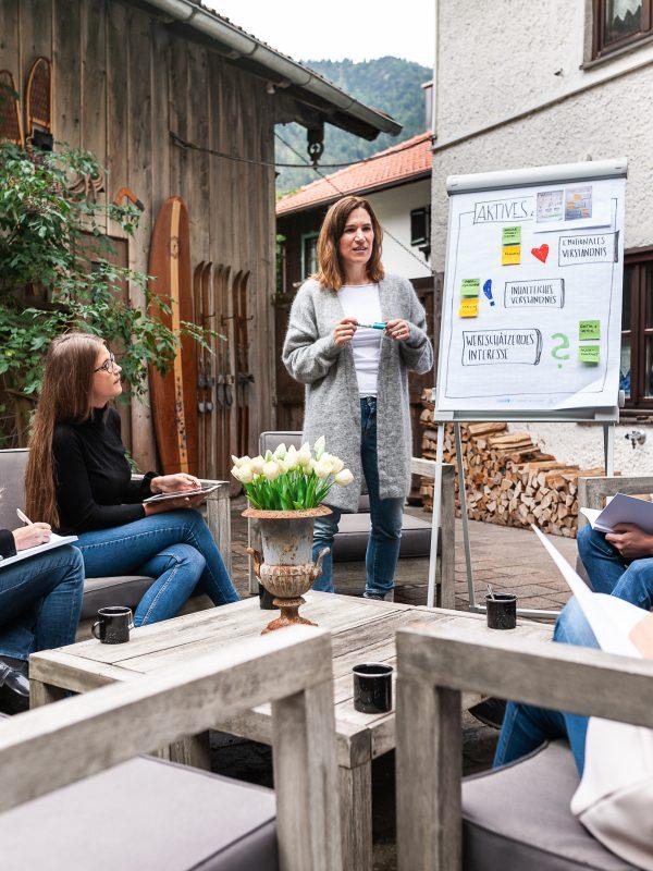 Tagungsgruppe hört der Vortragenden zur Präsentation auf der Terrasse des Dorfbad Tannermühl zu