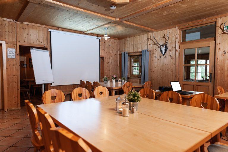 Seminartisch in der Kaminstube vor Leinwand mit Beamer