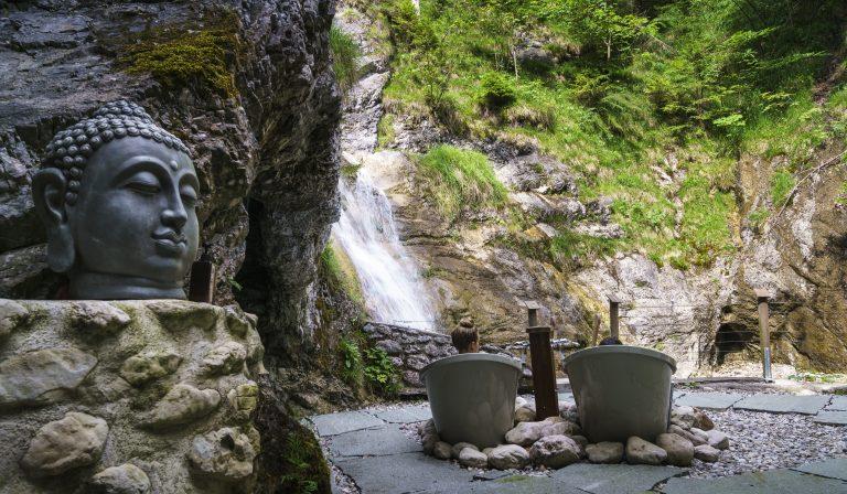 Badewannen am Wasserfall mit Buddha-Dekoration und Ausblick zum Gumpen-Tauchbecken am Dorfbad Tannermühl