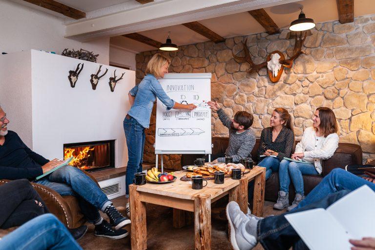 Workshop anhand Flipchart mit loderndem Kaminfeuer, um das sich die Tagungsgruppe im Dorfbad Tannermühl versammelt