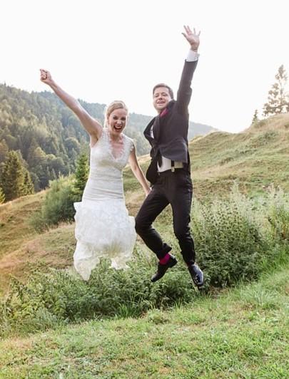 jubelnd springendes Brautpaar auf der Almwiese vorm Almbad Sillberghaus