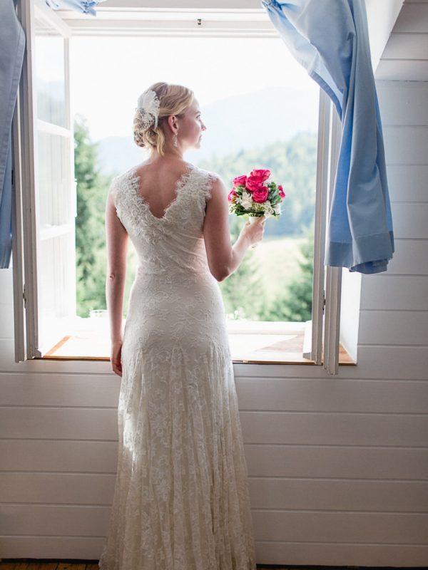 fertig gestylte Braut blickt aus dem Fenster des Almbad Sillberghaus (Rückenansicht)