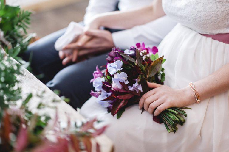 Alles im Griff: Brautstrauß in der linken, Bräutigam an der rechten Hand zur standesamtlichen Trauzeremonie im Almbad Huberspitz