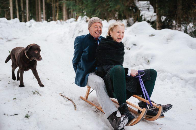 Im Winter: Brautpaar fährt gemeinsam auf dem Schlitten vom Almbad Huberspitz bergab, einer ihrer Hunde läuft hinterher