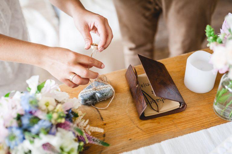 Die Braut nimmt den Ring für Ihren Ehemann vom Ringkissen, am dekorierten Trautisch im Alm-Standesamt Almbad Huberspitz