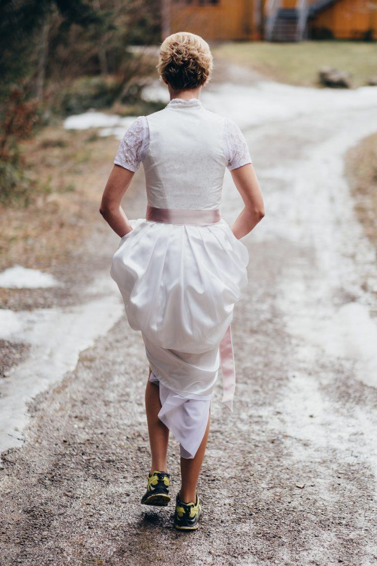 Braut mit angehobenem Brautkleid & Sneakers auf dem Weg durch die Natur zum Almbad Huberspitz