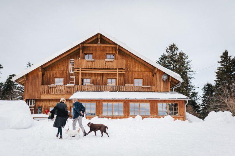 Brautpaar mit 2 Hunden auf dem Weg durch den Schnee zum Almbad Huberspitz im Winter zur standesamtlichen Trauung in 1.050m Höhe mit Blick auf die Berge