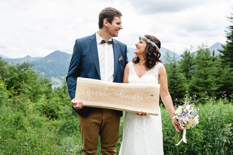 Das frisch vermählte Ehepaar vor Alpenpanorama des Almbad Huberspitz mit gemeinsam hochgehaltenem Holz-Schild
