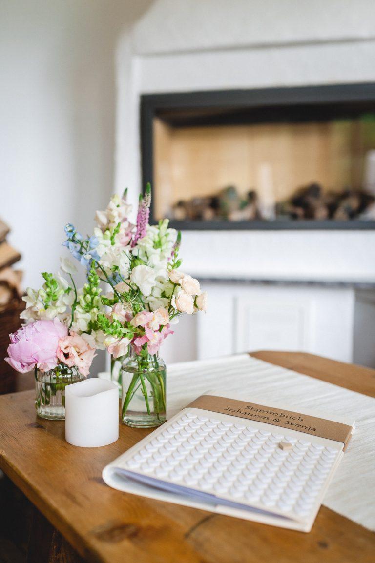 Stammbuch auf dem Trautisch, nebst frischen Blumen, im Hintergrund der Kamin im Wintergarten des Almbad Huberspitz