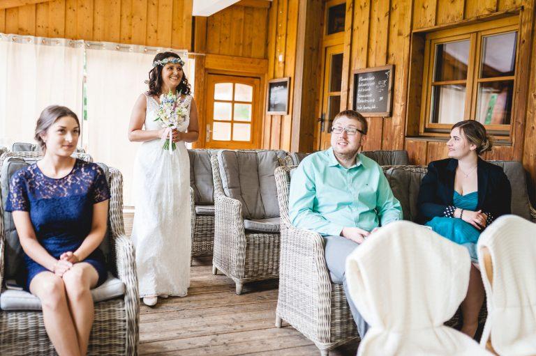 Die im weißen Brautkleid gekleidete Braut schreitet durch den Trausaal im Almbad Huberspitz, zur standesamtlichen Trauung in 1.050m Höhe mit Blick auf die Berge
