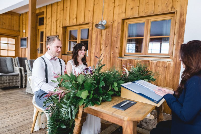 Ein besonderer Moment: das Brautpaar am Trautisch während der standesamtliche Trauung im Almbad Huberspitz