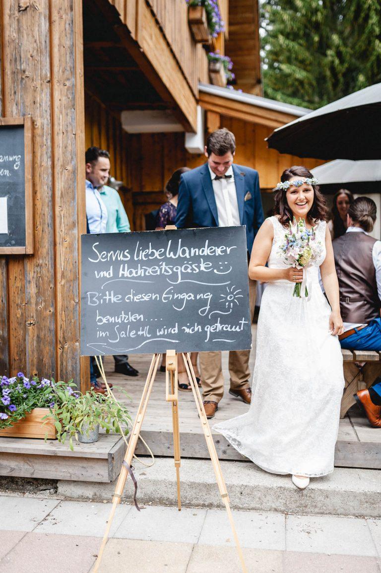 Das frisch vermählte Ehepaar verlässt das Salettl des Almbad Huberspitz vorbei am großen Hinweisschild für Wanderer