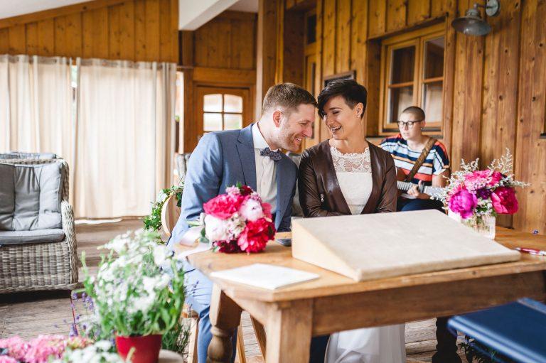 Das Brautpaar lacht am Trautisch - im Hintergrund spielt im Trausaal eine Musikerin an der Gitarre im Almbad Huberspitz