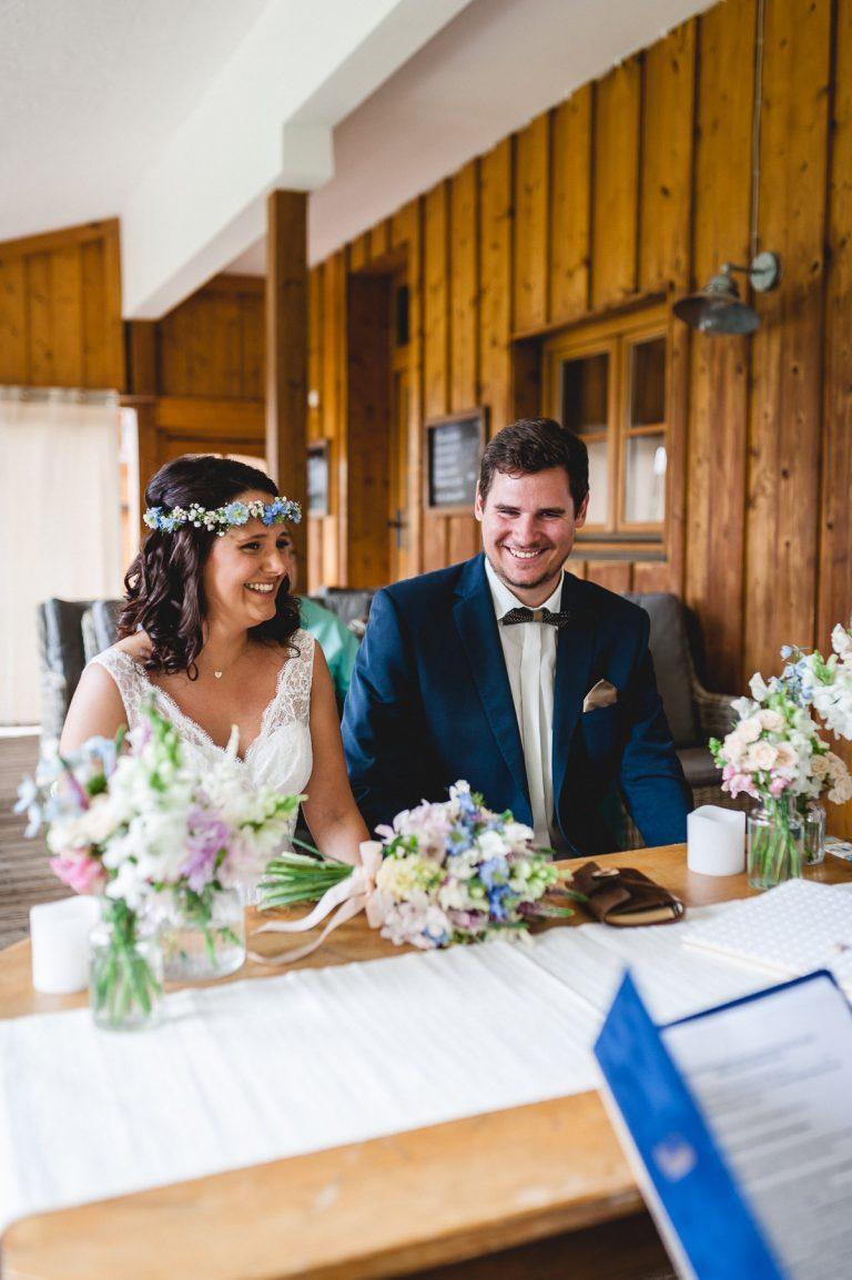 Lachendes Brautpaar am Trautisch, der mit Brautstrauß und zwei weiteren Blumensträußen dekoriert ist - Berg-Standesamt / Alm-Standesamt in 1.050m Höhe mit Blick auf die Berge