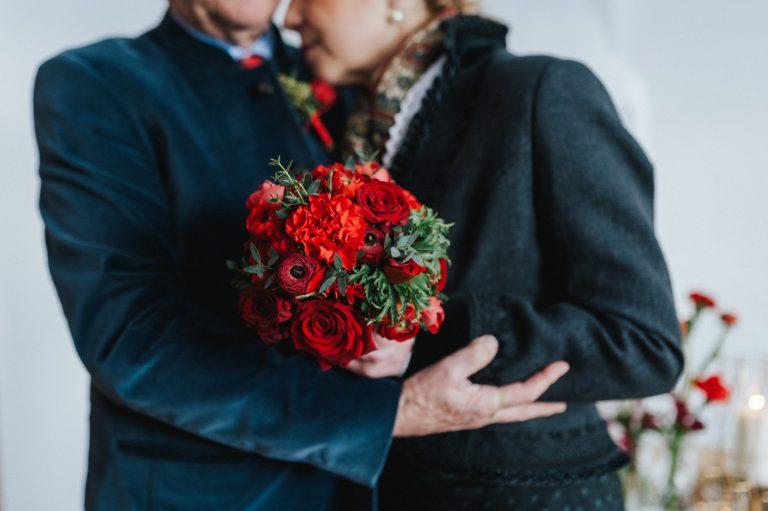 In warmen Farben im Winter: der Brautstrauß in rot-orange - gehalten vom umarmenden Brautpaar im Almbad Huberspitz