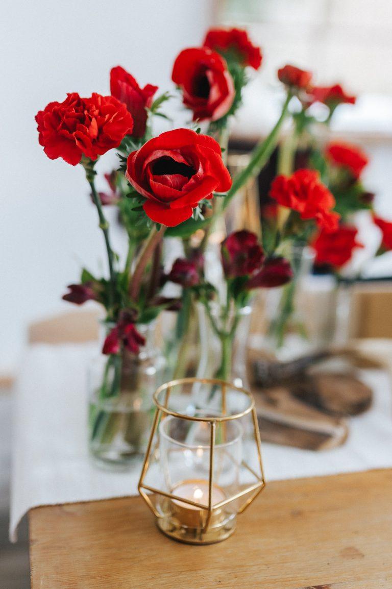 Rot-orange-farbene Blumen und Origami-Kerzenhalter als Dekoration am Trautisch des Almbad Huberspitz