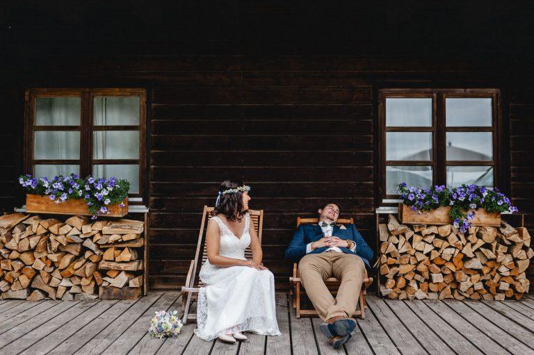 Brautpaar entspannt in den Liegestühlen auf der Sonnenterrasse, umrahmt von Stückholz und blühenden Fensterblumen