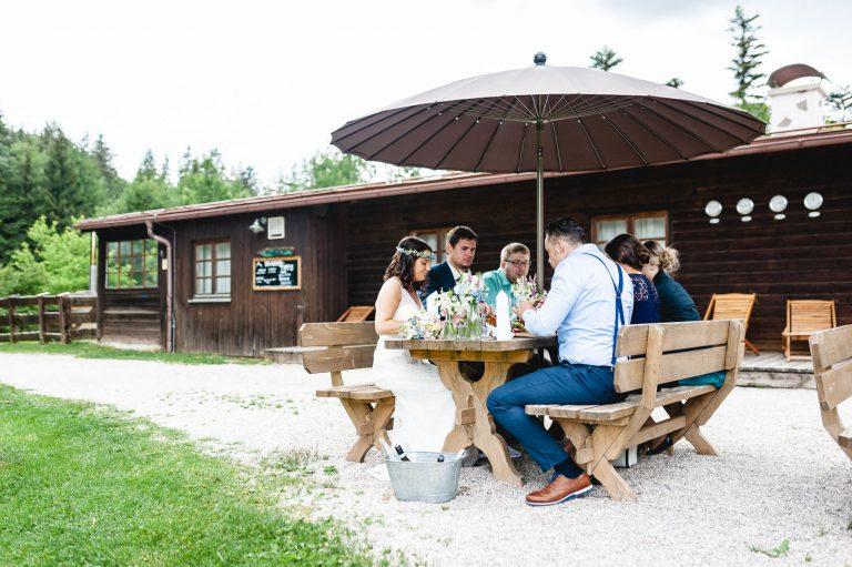 Das Brautpaar und Ihre Gäste sitzen zum Mittagessen auf den Holzgarnituren unter dem Sonnenschirm vorm Almbad Huberspitz