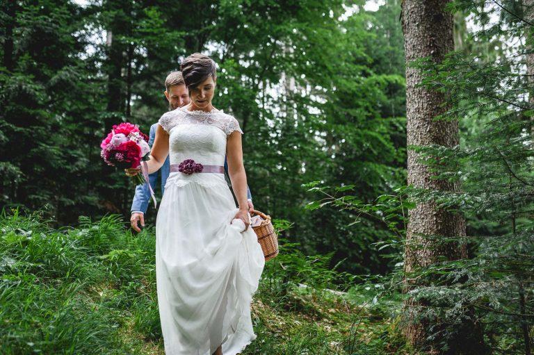 Das Brautpaar spaziert mit Brautstrauß und Picknickkorb durch den Bergwald am Almbad Huberspitz