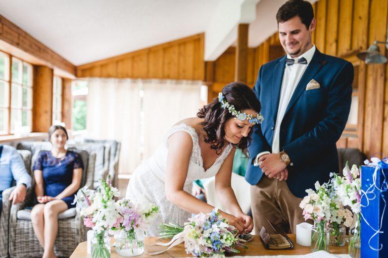 Ringtausch bei der standesamtlichen Trauung im Almbad Huberspitz, die Ringe liegen am floral dekorierten Trautisch bereit