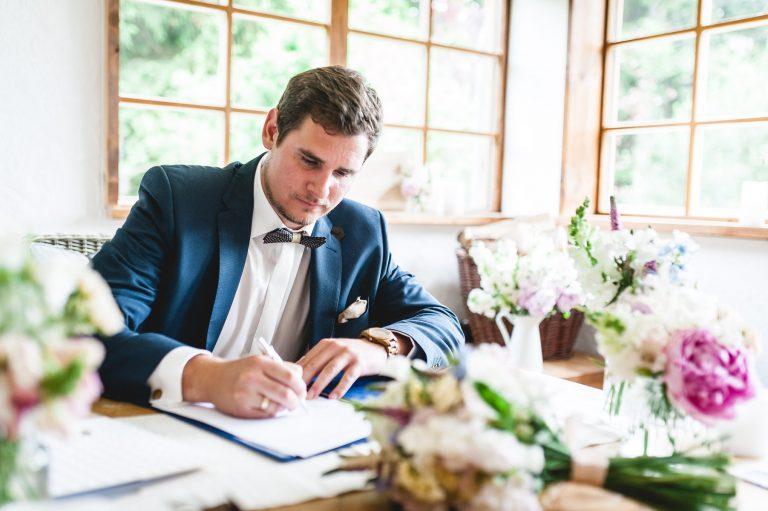 Urkundenunterzeichnung: Der Bräutigam unterschreibt urkundliches Dokument nach vollzogener standesamtlicher Trauung im Almbad Huberspitz