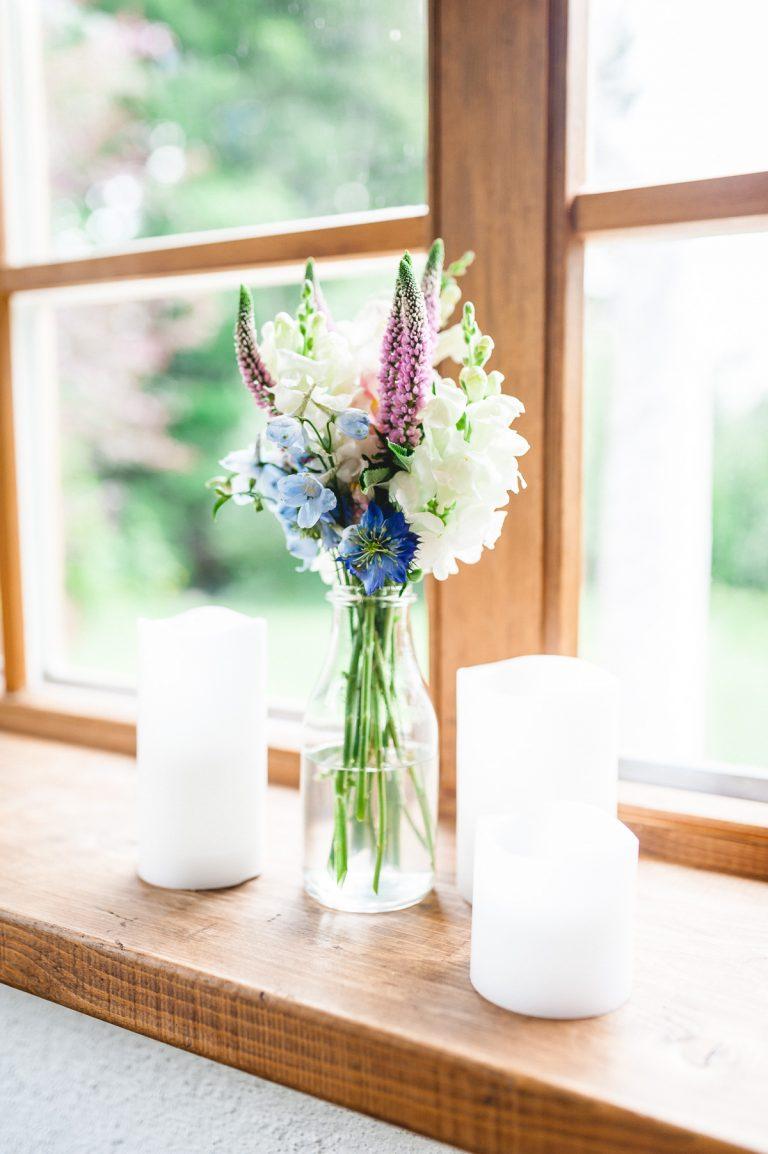 Blumenstrauß und Kerzen im Glas auf der Fensterbank im Wintergarten des Almbad Huberspitz