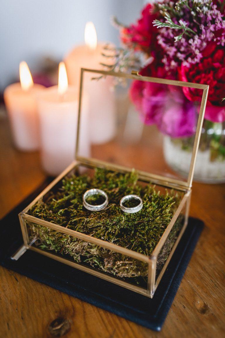 Eheringe gebettet auf Moos, neben Kerzen und dem Brautstrauß auf dem Trautisch im Almbad Huberspitz