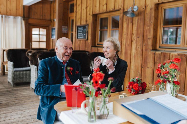 Das Brautpaar am Trautisch lacht, zückt gleichzeitig Taschentücher für den emotionalen Moment zur Trauung im Almbad Huberspitz