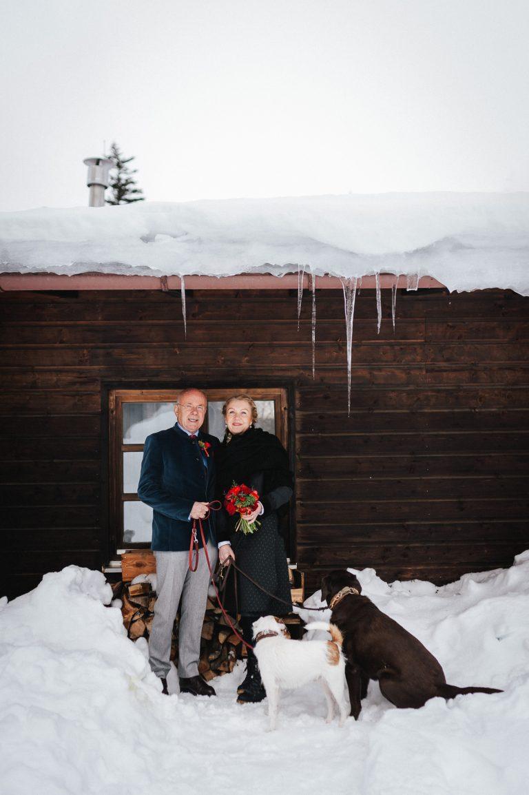 Brautpaar mit zwei Hunden vorm Almbad Huberspitz in winterlicher Hochzeitskulisse mit Eiszapfen