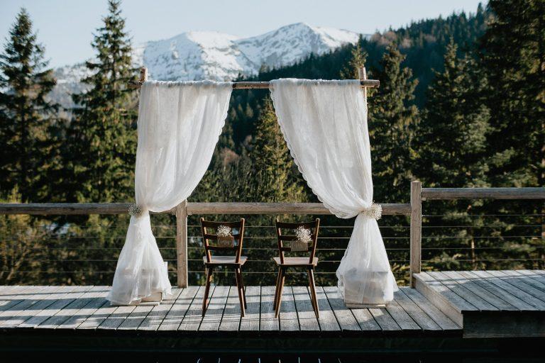 Traubogen mit Stühlen Mr und Mrs am Naturpool mit Blick auf die schneebedeckten Berge