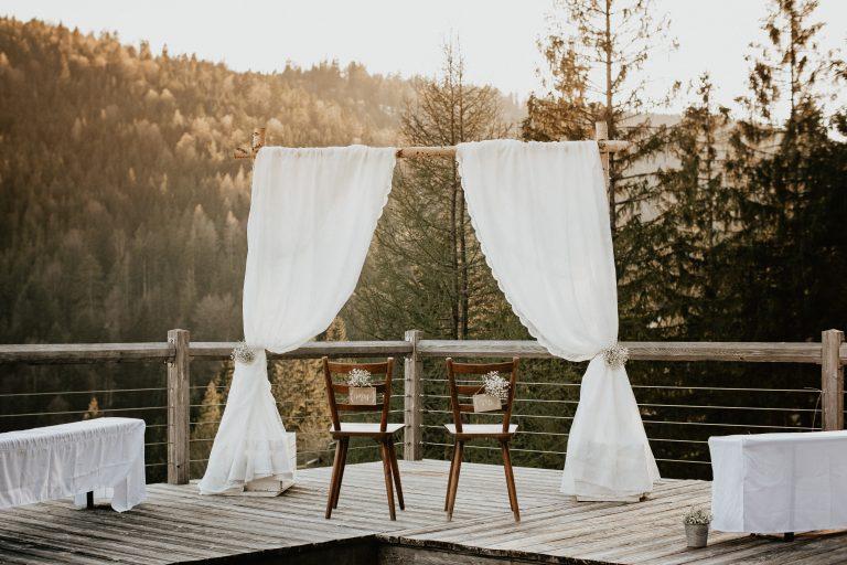 Traubogen mit Stühlen für das Brautpaar mit Blick zum Sonnenuntergang
