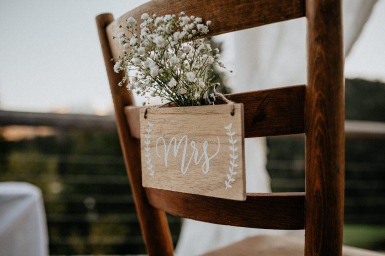 Mit Schleierkraut und Mrs-Schild dekorierter Brautstuhl