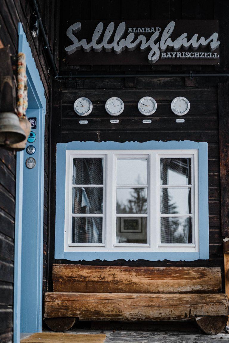 Der Eingangsbereich im Almbad Sillberghaus mit himmelblauen Fenstern und Weltuhren