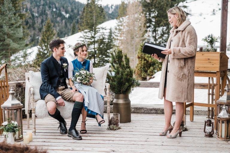Brautpaar auf dem Liebesbankerl vor der Traurednerin auf der Terrasse des Almbad Sillberghaus