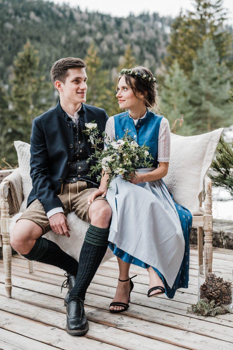 Verliebter Blick der Braut zu ihrem Bräutigam auf dem Liebesbankerl während der Trauung auf der Terrasse