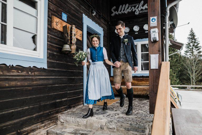 Brautpaar in Tracht vorm Eingangsbereich des Almbad Sillberghaus
