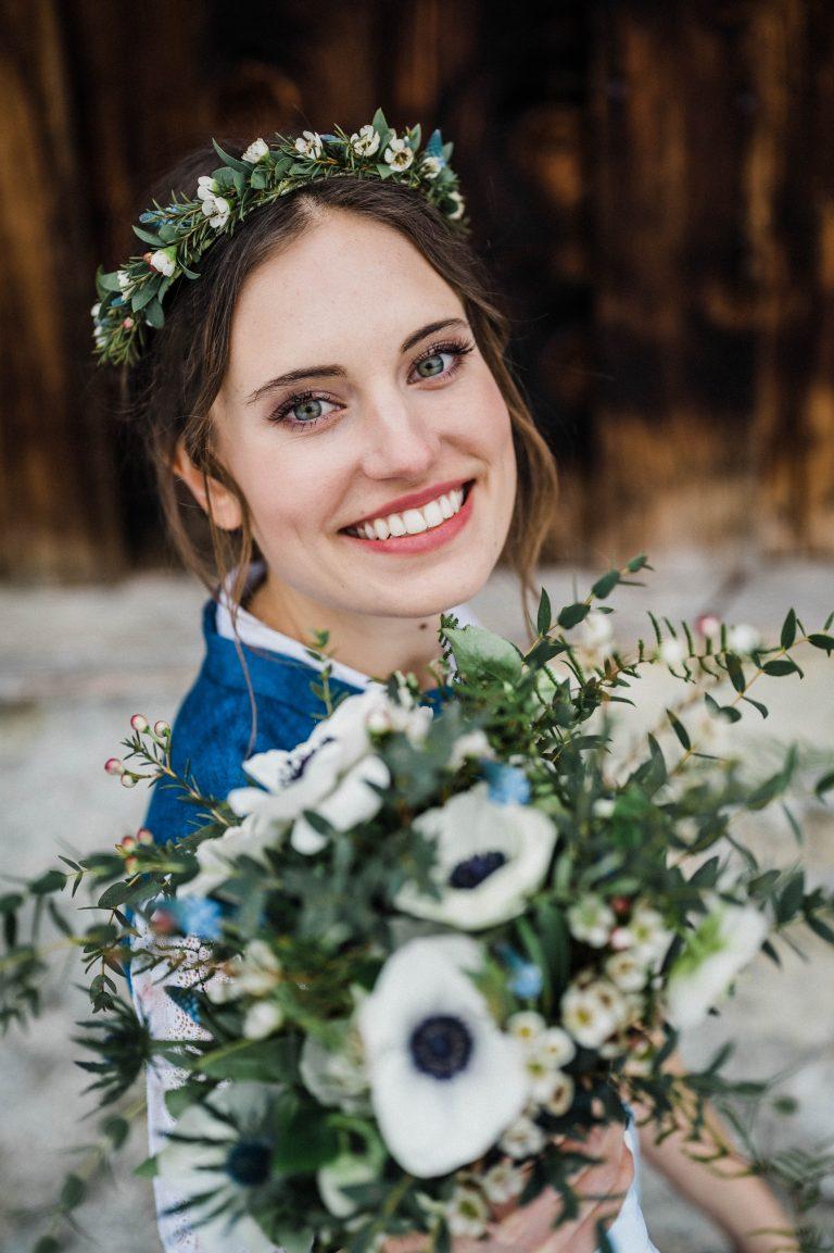 Glückliche Braut mit ihrem Brautstrauß vor dem Almbad Sillberghaus