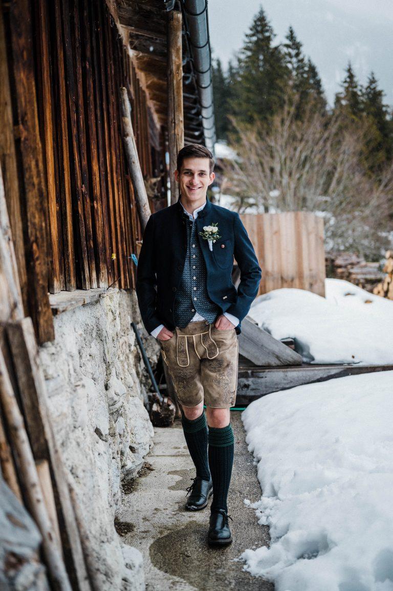 Der glückliche Bräutigam im Schnee vorm Almbad Sillberghaus