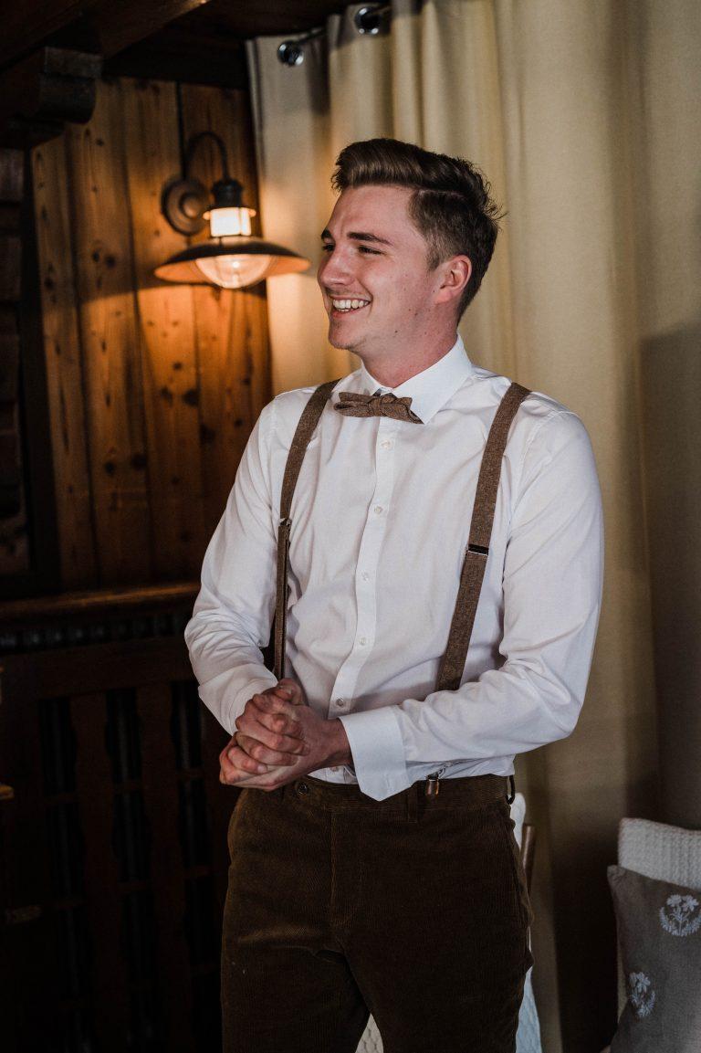 Bräutigam in Tracht lacht vorfreudig im Kaminzimmer des Almbad Sillberghaus