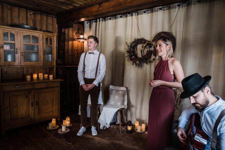 Bräutigam und Traurednerin warten auf die Braut zur Trauung im Kaminzimmer, Gitarrenspiel begleitet den Einzug