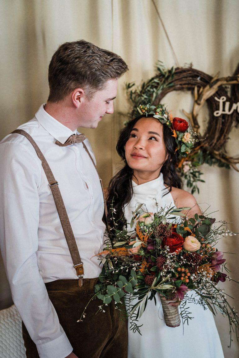 Brautpaar wechselt verliebte Blicke vor dem dekorierten Traubereich des Kaminzimmers