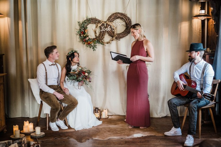 Das Brautpaar sitzend vor der Traurednerin, die von einem Gitarrenspieler im Kaminzimmer begleitet wird