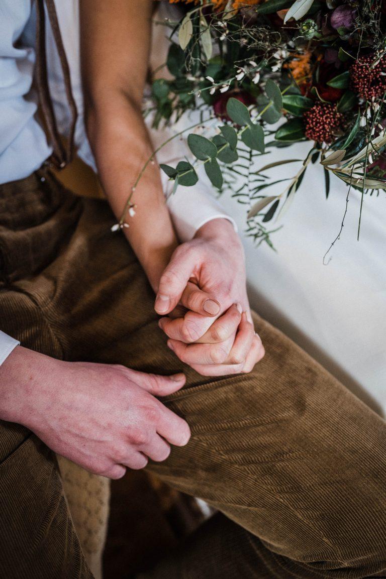Die Hände des Brautpaares sind eng verschlungen