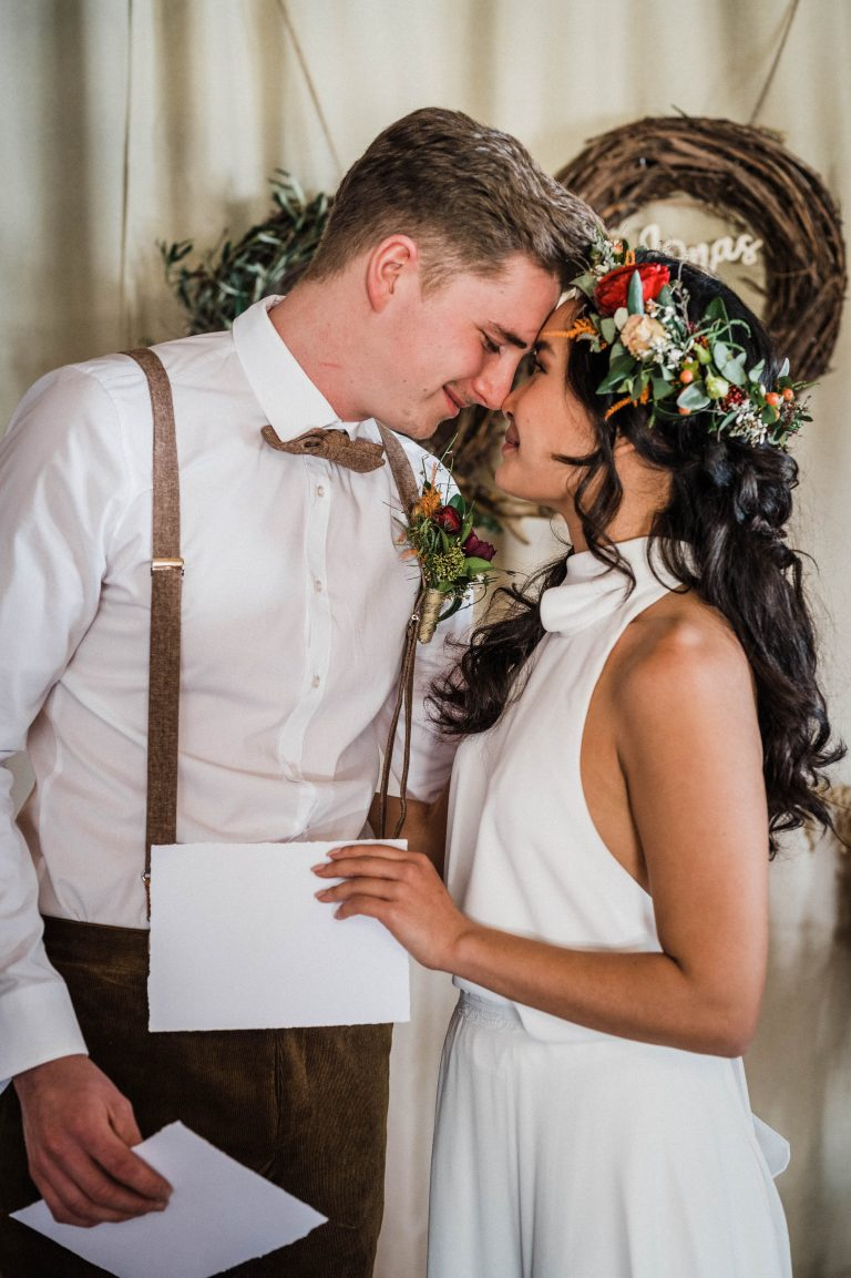 Das Brautpaar steckt die Köpfe zusammen, ihre Eheschwüre jeweils in der Hand