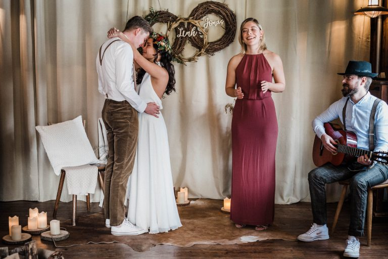 Brautpaar tanzt eng umschlungen, während die Traurednerin mit Gitarrenbegleitung singt im Kaminzimmer