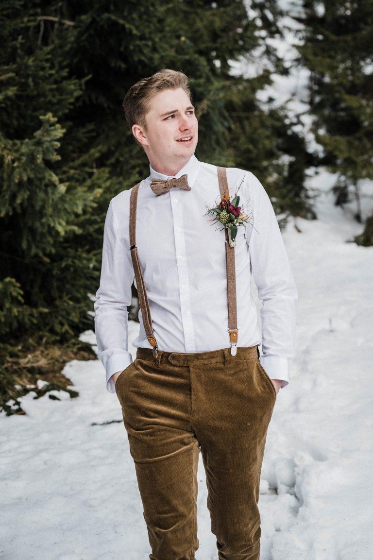 Bräutigam schreitet gemütlich durch den schneebedeckten Bergwald
