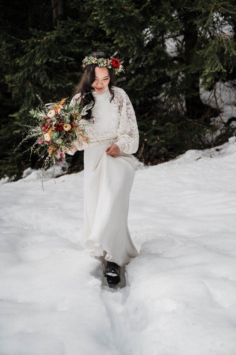 Braut in weiß folgt ihrem Bräutigam durch den Schnee